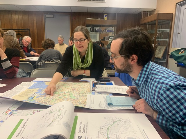 Nuala pointing to bus map at MTA meeting