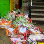 large colorful bags of food to be donated by COVID Care Neighborhood network